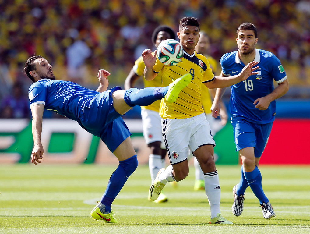. Greece\'s Kostas Katsouranis left, challenges Colombia\'s Teofilo Gutierrez during the group C World Cup soccer match between Colombia and Greece at the Mineirao Stadium in Belo Horizonte, Brazil, Saturday, June 14, 2014.  (AP Photo/Frank Augstein)