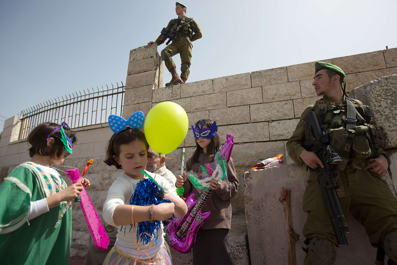 . Israeli soldiers secure the area as Israeli settler children dressed up in masks take part in a parade to celebrate the Jewish holiday of Purim in al-Shuhada Street, in the West Bank town of Hebron, on March 16, 2014. The carnival-like Purim holiday is celebrated with parades and costume parties to commemorate the deliverance of the Jewish people from a plot to exterminate them in the ancient Persian Empire 2,500 years ago, as recorded in the Biblical Book of Esther. (MENAHEM KAHANA/AFP/Getty Images)