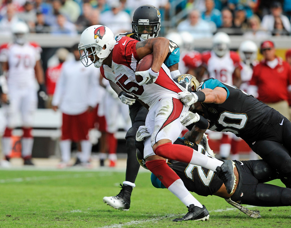 . Arizona Cardinals wide receiver Michael Floyd (15) breaks tackles by Jacksonville Jaguars cornerback Will Blackmon (24), free safety Josh Evans, bottom, and outside linebacker Russell Allen, right, for a 91-yard touchdown in the second half of an NFL football game in Jacksonville, Fla., Sunday, Nov. 17, 2013. (AP Photo/Stephen Morton)