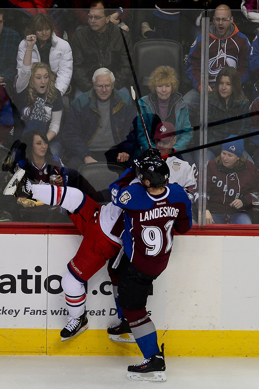 . Gabriel Landeskog (92) of the Colorado Avalanche checks Cam Atkinson (13) of the Columbus Blue Jackets during the second period. The Colorado Avalanche hosted the Columbus Blue Jackets at the Pepsi Center on Tuesday, December 31, 2013. (Photo by AAron Ontiveroz/The Denver Post)