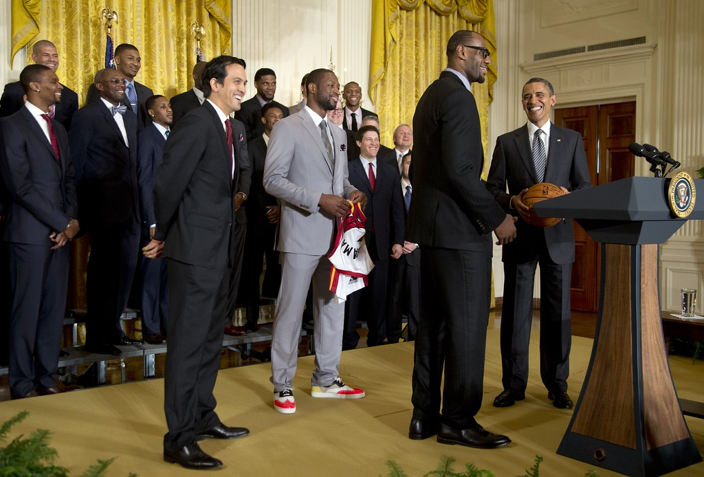 . President Barack Obama stands with a signed basketball from Miami Heat forward LeBron James, second from right, forward Dwyane Wade, third from right in gray, and coach Erik Spoelstra as he welcomes the NBA basketball champion Miami Heat, to the East Room of the White House, Monday, Jan. 28, 2013, in Washington. (AP Photo/Carolyn Kaster)
