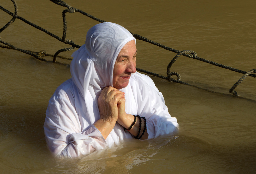 . A Christian Orthodox pilgrim immerses herself into the waters of the Jordan River during a baptism ceremony marking the epiphany on January 18, 2014 at the Qasr al-Yahud baptismal site in the West Bank. For Christians, the Epiphany celebrates the baptism of Christ by John the Baptist in the river Jordan. AHMAD GHARABLI/AFP/Getty Images