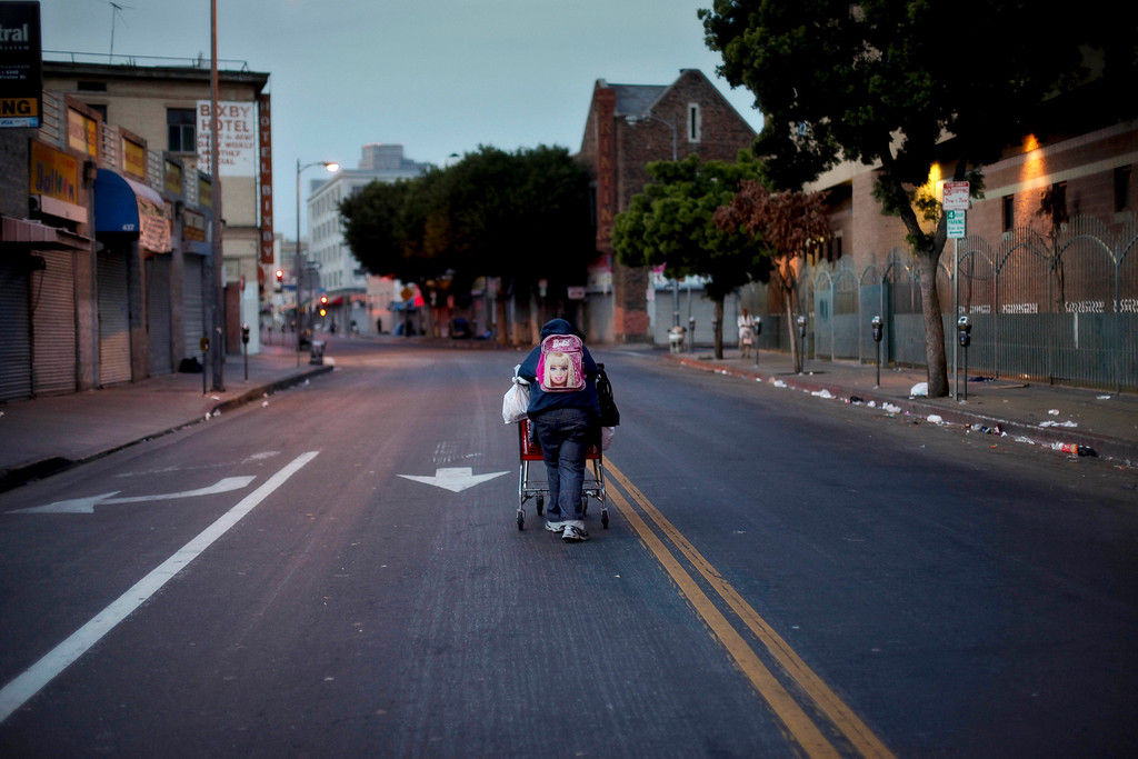 . Wearing a Barbie backpack, a homeless woman pushes a shopping cart full of her belongings in the middle of the street in the Skid Row area of Los Angeles, Tuesday, March 19, 2013. (AP Photo/Jae C. Hong)