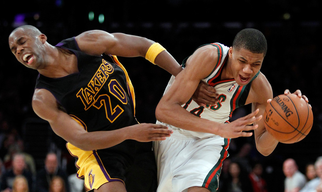 . Los Angeles Lakers guard Jodie Meeks (20) collides with Milwaukee Bucks guard Giannis Antetokounmpo (34) during the second half of an NBA basketball game Tuesday, Dec. 31, 2013, in Los Angeles. The Bucks won 94-79. (AP Photo/Alex Gallardo)