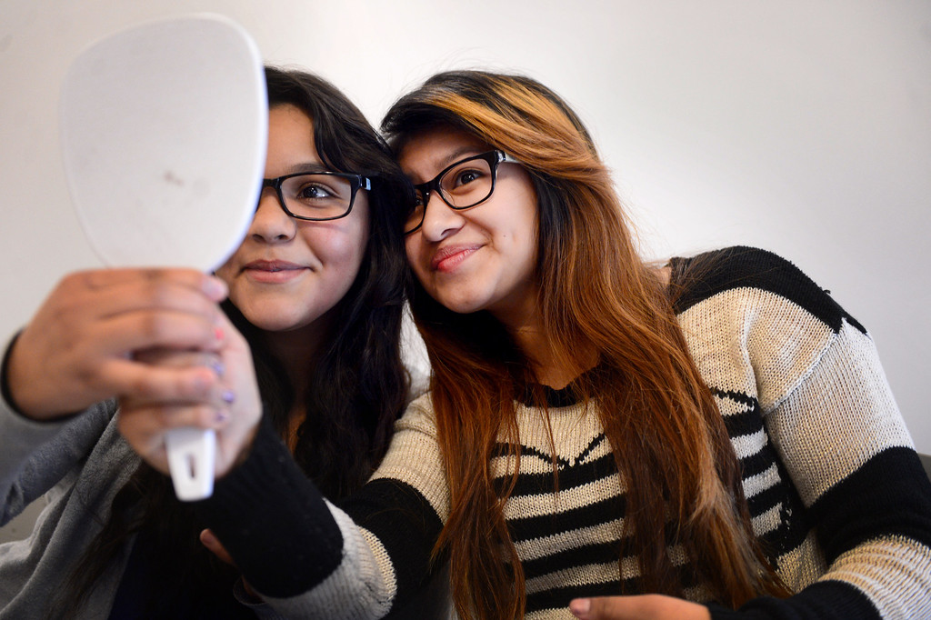 . From left, Cyndy Lopez and Yesenia Garcia, both 15 and 10th graders at Montebello Unified School District�s Applied Technology Center (ATC) High School, choose free eye glasses from Helen Keller�s International ChildSight Los Angeles program Friday, February 7, 2014. The group has screened 15,000 students in Los Angeles County with 2,000 receiving glasses. (Photo by Sarah Reingewirtz/Pasadena Star-News)