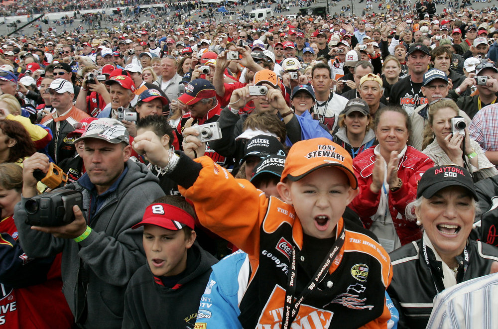 Description of . Five-year-old Nicholas Blaney, front, of Vermont, yells for his favorite driver during introductions prior to the start of the Daytona 500 auto race at Daytona International Speedway in Daytona Beach, Fla., Sunday, Feb. 19, 2006. (AP Photo/John Raoux)