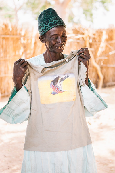 A village chief accepts a T-shirt sporting a Montagu's harrier. Without the approval of local communities it would not be possible to carry out research in this region. Khelcom, Senegal.