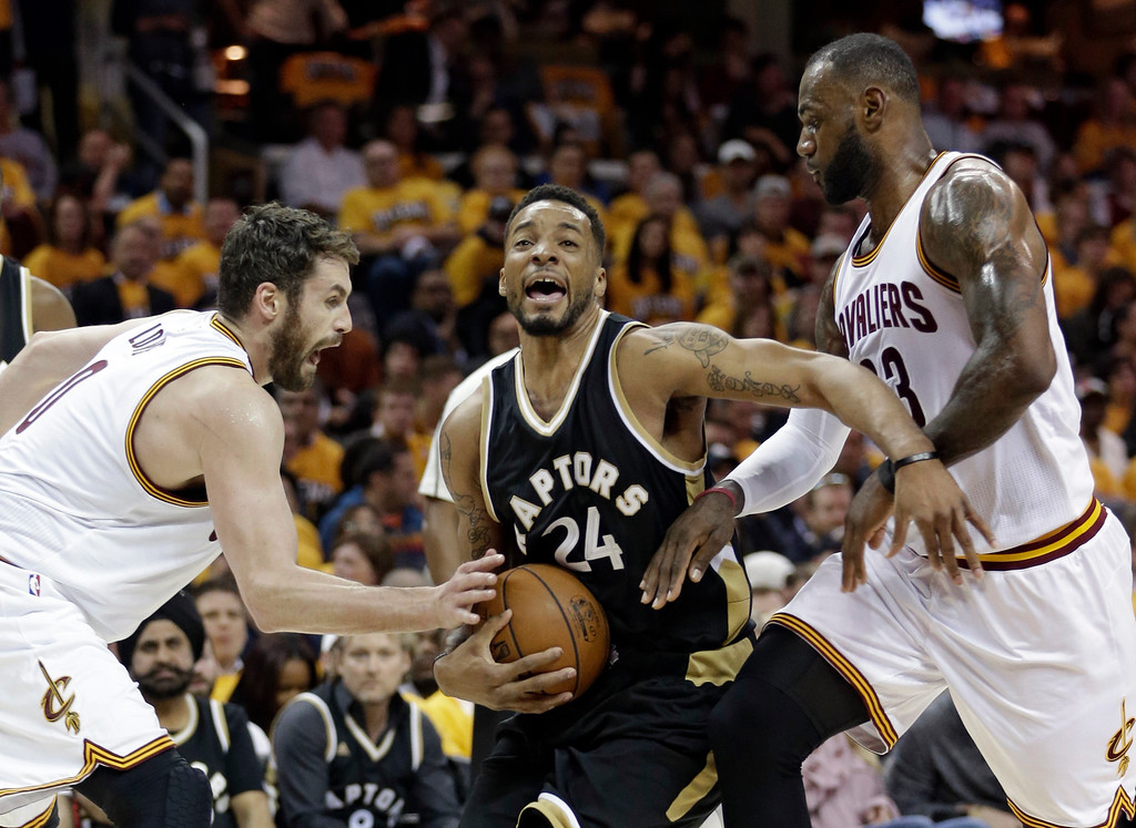 . Toronto Raptors\' Norman Powell, center, drives between Cleveland Cavaliers\' Kevin Love, left, and LeBron James during the first half in Game 2 of a second-round NBA basketball playoff series, Wednesday, May 3, 2017, in Cleveland. (AP Photo/Tony Dejak)