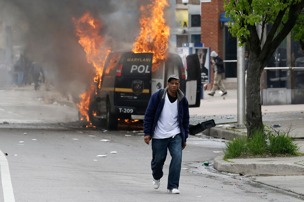 . A man walks past a burning police vehicle, Monday, April 27, 2015, during unrest following the funeral of Freddie Gray in Baltimore. Gray died from spinal injuries about a week after he was arrested and transported in a Baltimore Police Department van. (AP Photo/Patrick Semansky)