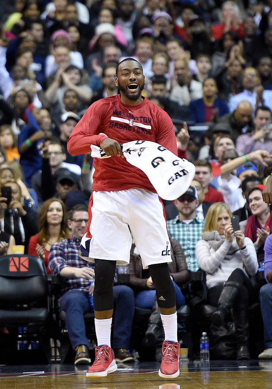 . Washington Wizards guard John Wall cheers his teammates during the second half of an NBA basketball game against the Denver Nuggets, Friday, Dec. 5, 2014, in Washington. (AP Photo/Nick Wass)