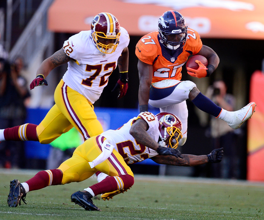 . Denver Broncos running back Knowshon Moreno (27) jumps over Washington Redskins cornerback DeAngelo Hall (23) in the third quarter. The Denver Broncos take on the Washington Redskins at Sports Authority Field at Mile High in Denver on October 27, 2013. (Photo by AAron Ontiveroz/The Denver Post)