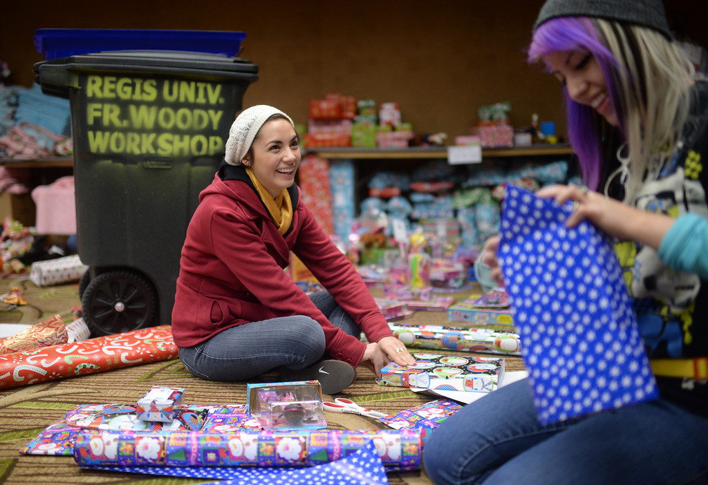 ". DENVER, CO. DECEMBER 21: Andreina Lujan, 19, of Denver, left, and her sister Alejandra, 21, are  wrapping Christmas gift during the annual Father Woody Christmas Party in Denver, Colorado December 21, 2013. In advance of handing out 5,000 gifts, volunteers are doing a ""wrapping party\"" at the Sheraton Denver Downtown Hotel. (Photo by Hyoung Chang/The Denver Post)"