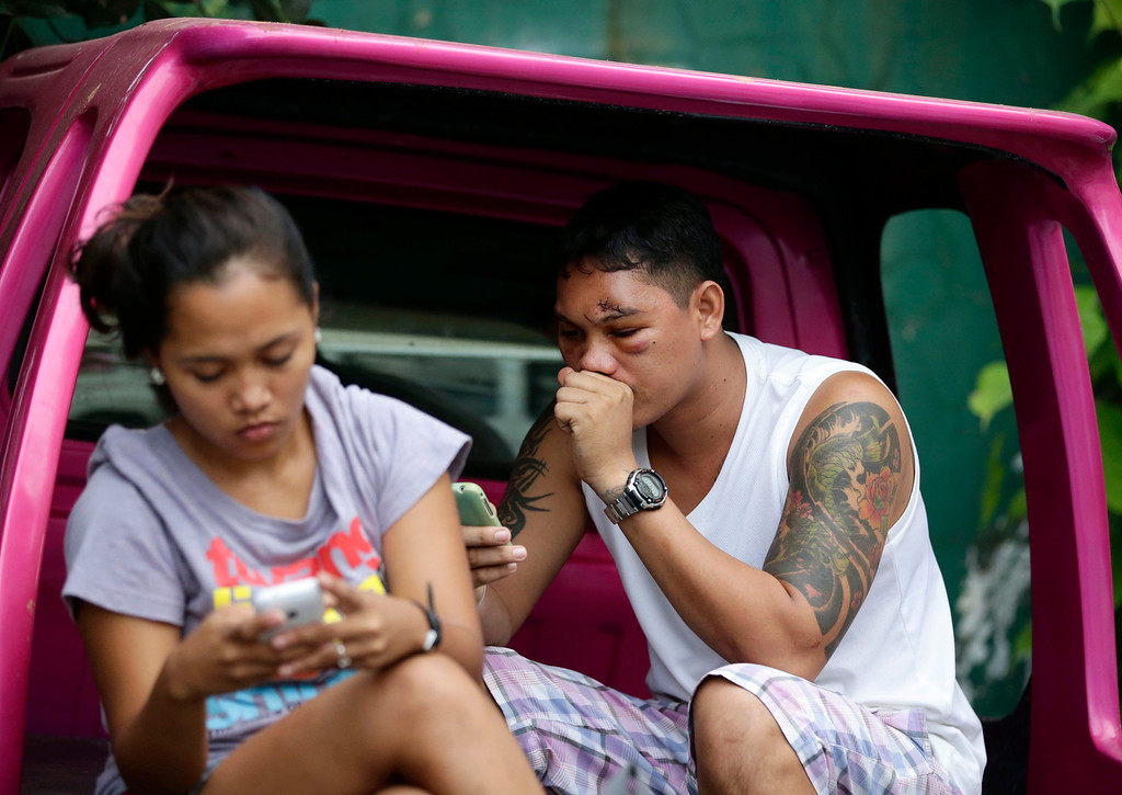 . An earthquake victim, right, sits in his vehicle outside a government hospital following a 7.2-magnitude earthquake that hit Cebu city in central Philippines Tuesday, Oct. 15, 2013. (AP Photo/Bullit Marquez)