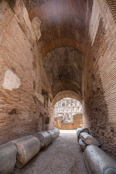 Walkway from the concession stands to the interior of the Colosseum, with old decorative columns along the side.