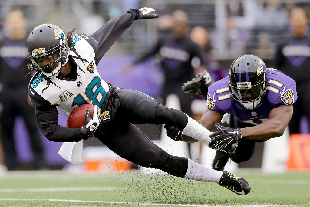 . Jacksonville Jaguars wide receiver Ace Sanders (18) is knocked off his feet by Baltimore Ravens wide receiver Kamar Aiken (11) on a kickoff return during the first half of an NFL football game in Baltimore, Sunday, Dec. 14, 2014. (AP Photo/Patrick Semansky)