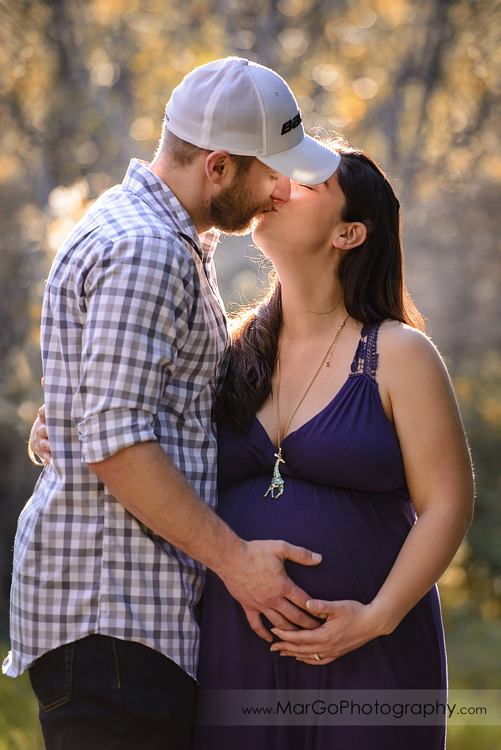 man in checkered shirt and pregnant woman in long violet dress kissing during maternity session at Ulistac Natural Area in Santa Clara