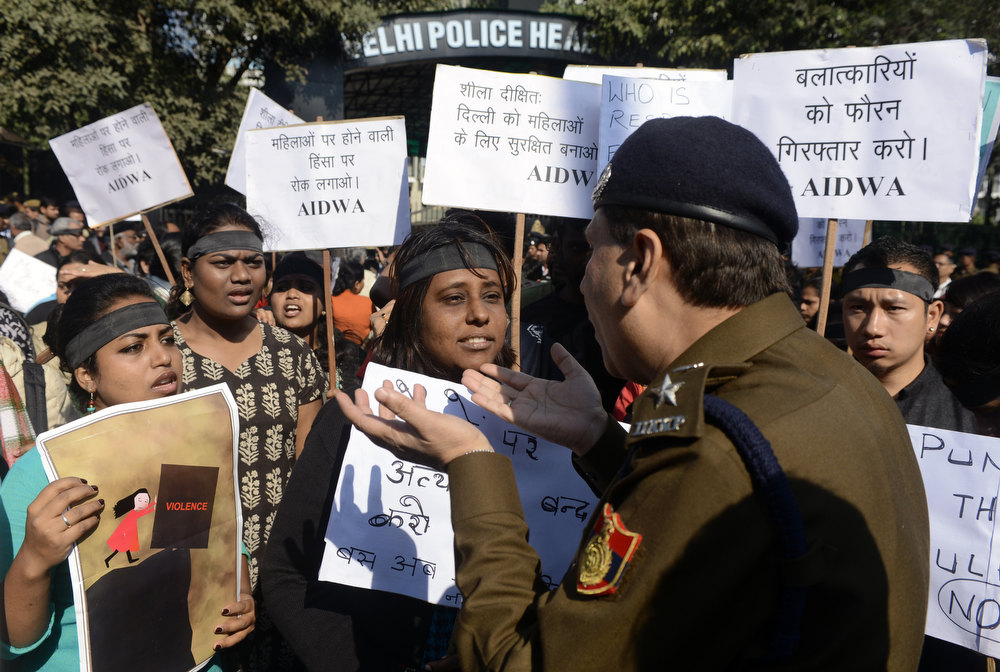 Description of . A policeman talks with demonstrators gathered outside the police headquarters as they protest against the gang-rape of a student in New Delhi on December 19, 2012. Four people, including the bus driver, have so far been arrested, while a hunt is ongoing for two other suspects. The attack sparked new calls for greater security for women in New Delhi, which registered 568 rapes in 2011 compared with 218 in India's financial capital Mumbai the same year. SAJJAD HUSSAIN/AFP/Getty Images