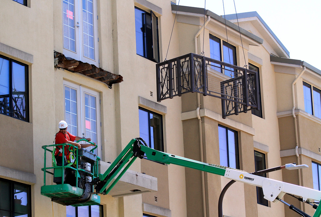 . A crane lifts the railing off the lower balcony in preparation for removing it outside the residential apartment building on Kittredge Street in Berkeley, Calif. on Wednesday, June 17, 2015.  Six people died and seven others were seriously injured when the balcony collapsed early Tuesday morning during a birthday party. (Laura A. Oda/Bay Area News Group)