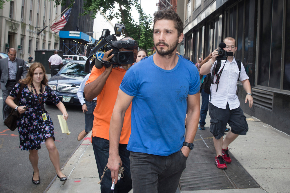 """. Actor Shia LaBeouf walks through the media after leaving Midtown Community Court following his arrest the previous day for yelling obscenities at the Broadway show \""""Cabaret,\"""" Friday, June 27, 2014, in New York. The 28-year-old star of the \""""Transformers\"""" franchise faces charges that include disorderly conduct and criminal trespass.  (AP Photo/John Minchillo)"""