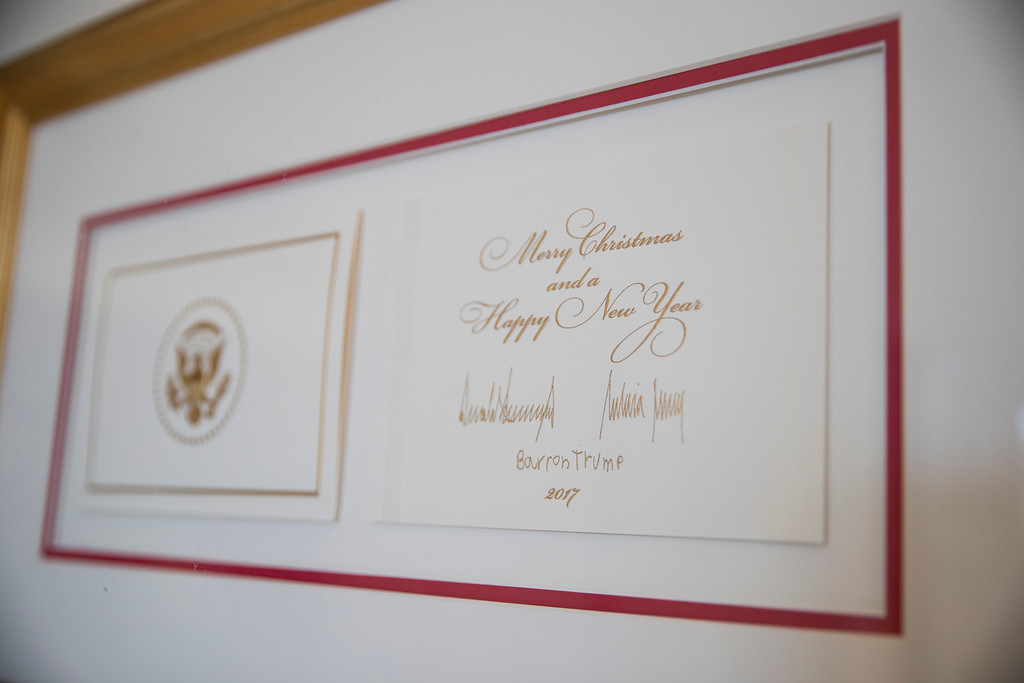 . The official White House Christmas card signed by President Donald Trump, first lady Melania Trump, and their son Barron Trump is seen in the East Garden Room during a media preview of the 2017 holiday decorations at the White House in Washington, Monday, Nov. 27, 2017. (AP Photo/Carolyn Kaster)