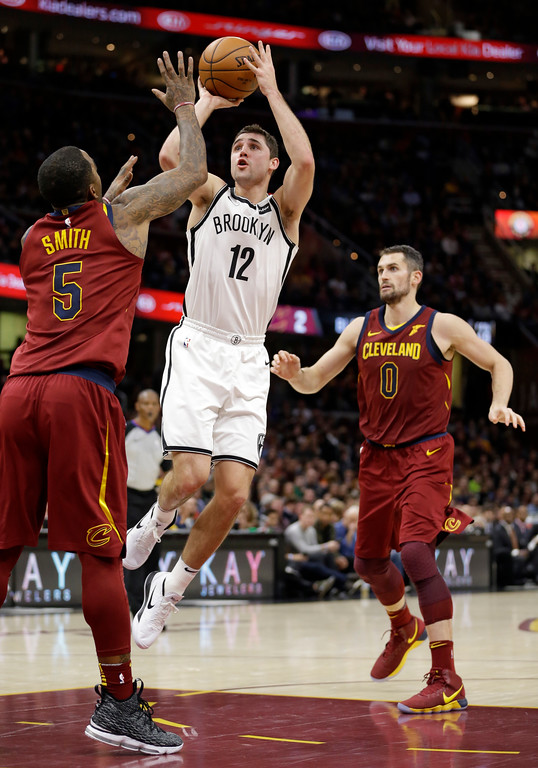 . Brooklyn Nets\' Joe Harris (12) shoots between Cleveland Cavaliers\' JR Smith (5) and Kevin Love (0) during the first half of an NBA basketball game, Wednesday, Nov. 22, 2017, in Cleveland. (AP Photo/Tony Dejak)