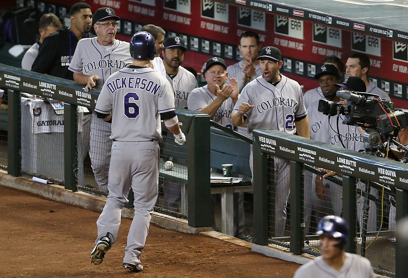 . Manager Walt Weiss #22 of the Colorado Rockies congratulates Corey Dickerson #6 after Dickerson hit a solo home-run against the Arizona Diamondbacks during the tenth inning of the MLB game at Chase Field on August 10, 2014 in Phoenix, Arizona. The Rockies defeated the Diamondbacks 5-3 in 10 innings. (Photo by Christian Petersen/Getty Images)