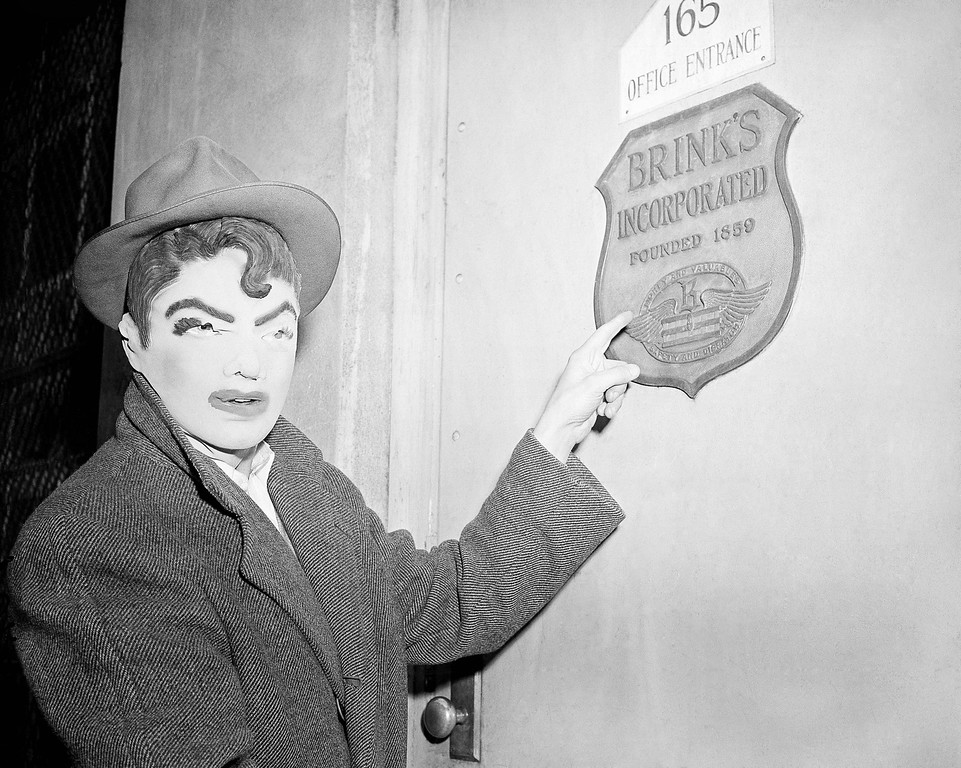 . A newsman wears a rubber mask similar to that worn by seven bandits who robbed Brink\'s armored car firm in Boston of $1, 50,000, Jan. 18, 1950. The reporter points to name plate on first of six locked doors opened by the gunmen. Mask was one of several purchased in joke shops by newsmen and police to see if they resembled description given by Brink\'s employees. (AP Photo)