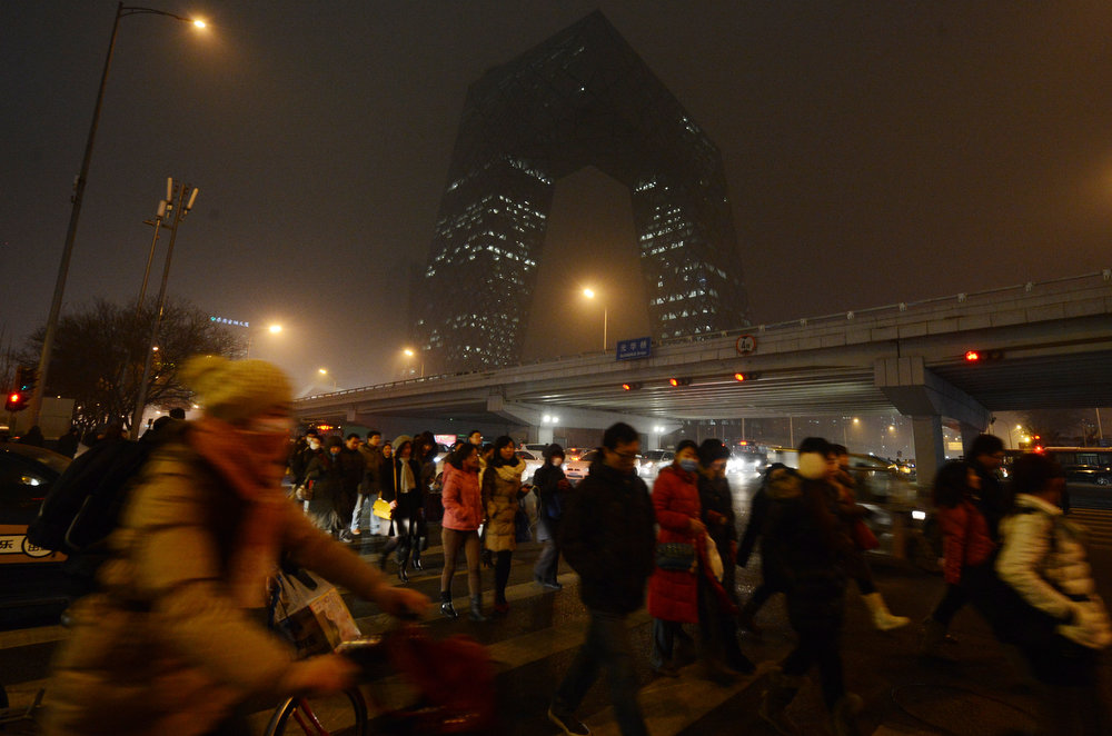 Description of . Chinese commuters wear face masks as they pass by the new CCTV building during heavy air pollution in Beijing on January 30, 2013.  Beijing urged residents to stay indoors as emergency measures were rolled out aimed at countering a heavy cloud of smog blanketing the Chinese capital and swathes of the country. The municipal government said children, the elderly and people sensitive to poor air quality should remain indoors, after authorities announced the closure of 103 factories and ordered 30 percent of official cars off the road.  MARK RALSTON/AFP/Getty Images