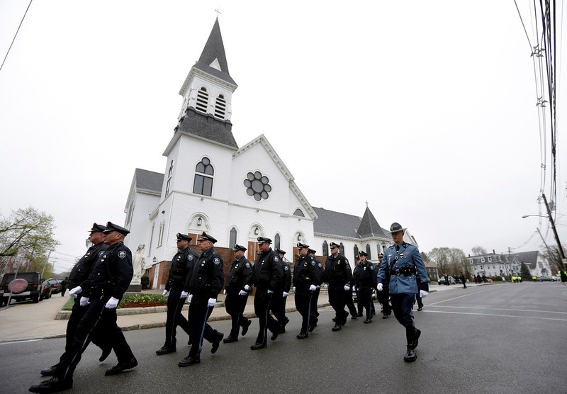 . Massachusetts Institute of Technology police officers march as they depart St. Patrick\'s Church in Stoneham, Mass., following a funeral Mass for MIT police officer Sean Collier, Tuesday, April 23, 2013. Collier was fatally shot on the MIT campus Thursday, April 18, 2013. Authorities allege that the Boston Marathon bombing suspects were responsible. Law enforcement official at right is unidentified. (AP Photo/Steven Senne)