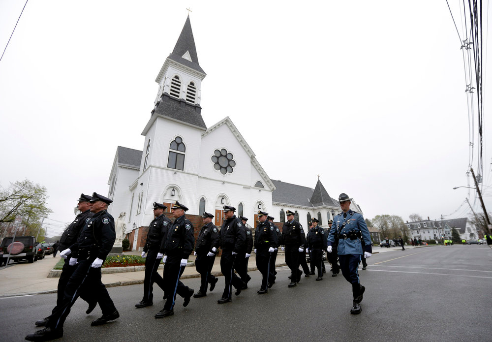 Description of . Massachusetts Institute of Technology police officers march as they depart St. Patrick's Church in Stoneham, Mass., following a funeral Mass for MIT police officer Sean Collier, Tuesday, April 23, 2013. Collier was fatally shot on the MIT campus Thursday, April 18, 2013. Authorities allege that the Boston Marathon bombing suspects were responsible. Law enforcement official at right is unidentified. (AP Photo/Steven Senne)