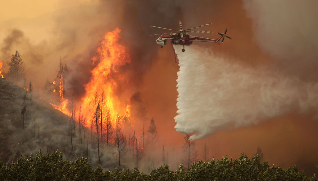 . Helicopters battle the 64,000 acre Beaver Creek Fire on Friday, Aug., 16, 2013 north of Hailey, Idaho. A number of residential neighborhoods have been evacuated because of the blaze.(AP Photo/Times-News, Ashley Smith)
