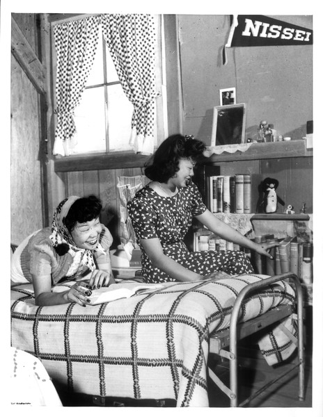 """""""Oko Murata, left, and Esther Naito, former office workers, evacuees now living at the Manzanar relocation center, proudly smile at the personal library they have established in their camp dormitory quarters.""""--caption on photograph"""