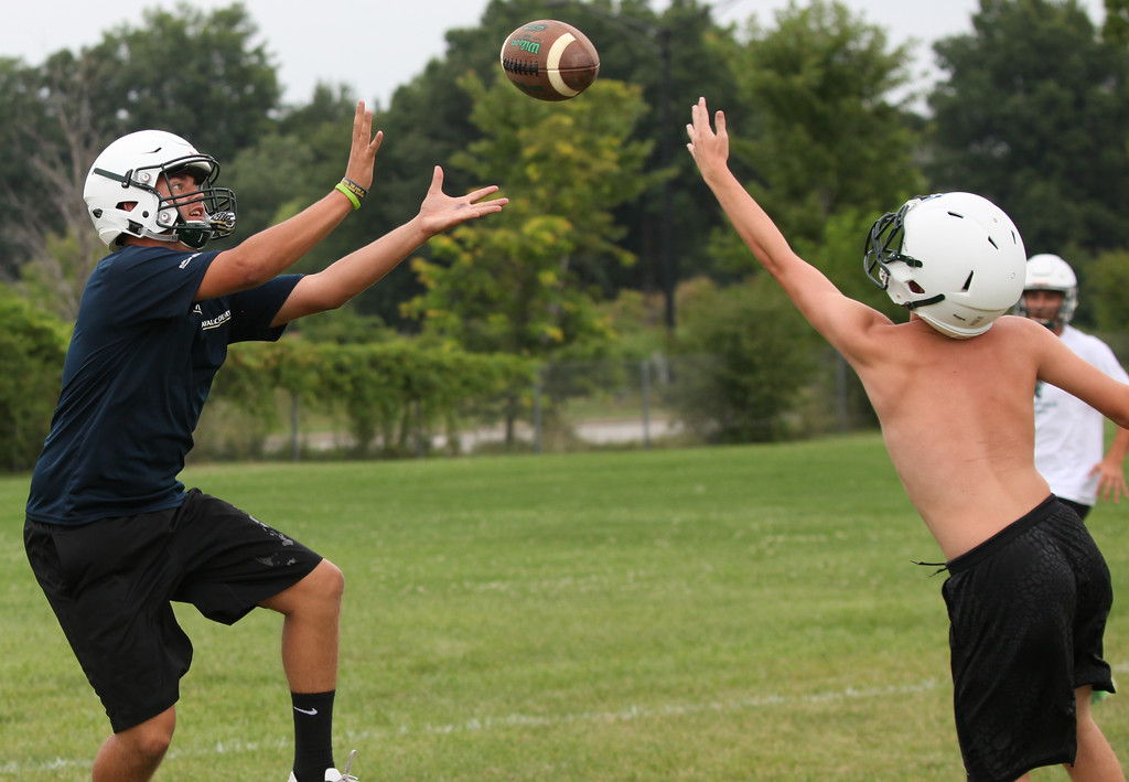 . Randy Meyers - The Morning Journal<br> Elyria Catholic\'s Asa Kempton makes a catch over a defender during Panther Ball at Elyria Catholic\'s first football practice on July 30.