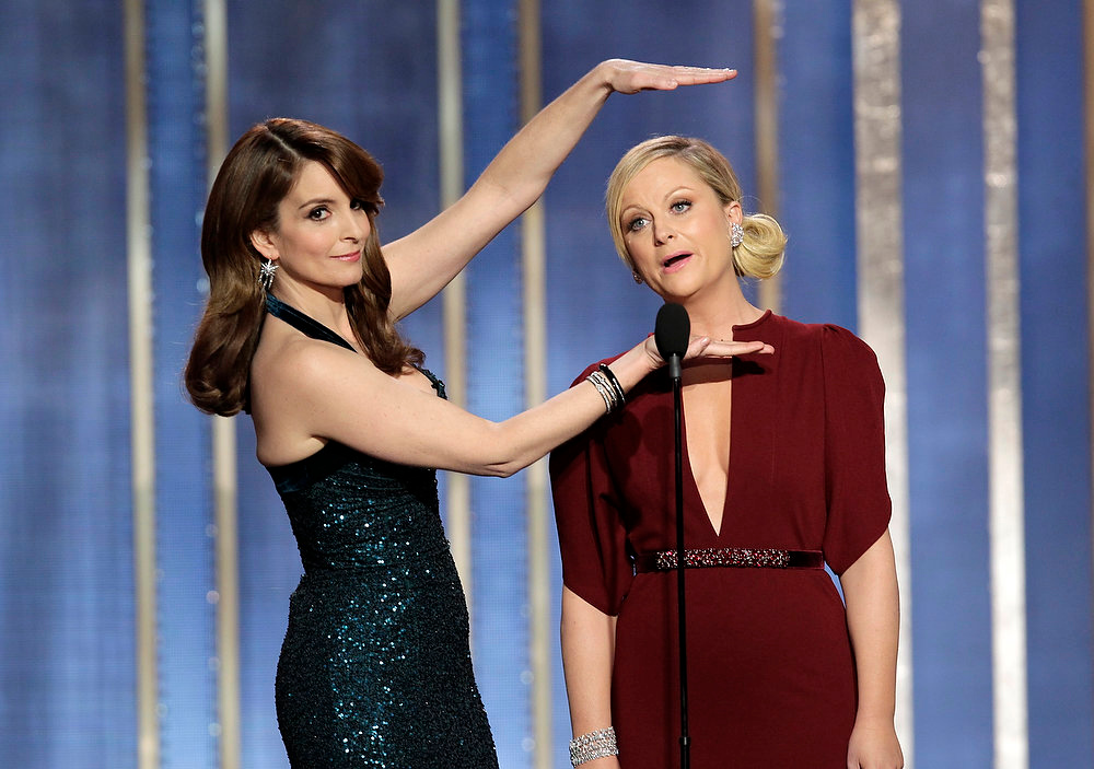 Description of . This image released by NBC shows co-hosts Tina Fey, left, and Amy Poehler on stage during the 70th Annual Golden Globe Awards held at the Beverly Hilton Hotel on Sunday, Jan. 13, 2013, in Beverly Hills, Calif. (AP Photo/NBC, Paul Drinkwater)