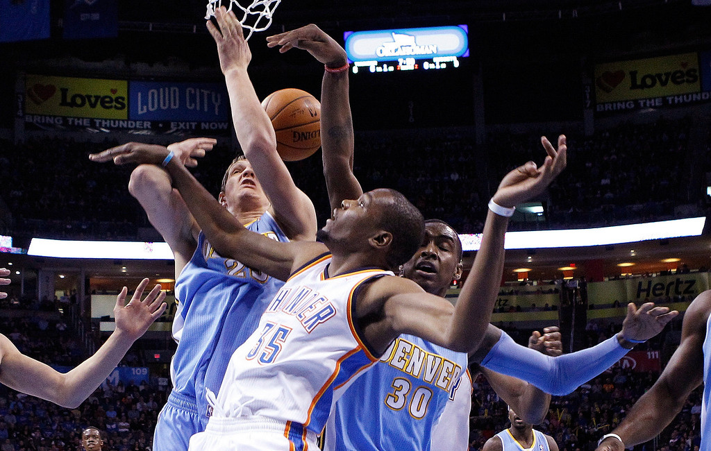 . Oklahoma City Thunder forward Kevin Durant (35) loses the ball under the basket in front of Denver Nuggets center Timofey Mozqov (25) and forward Quincy Miller (30) in the first quarter of an NBA basketball game in Oklahoma City, Monday, March 24, 2014. (AP Photo/Sue Ogrocki)