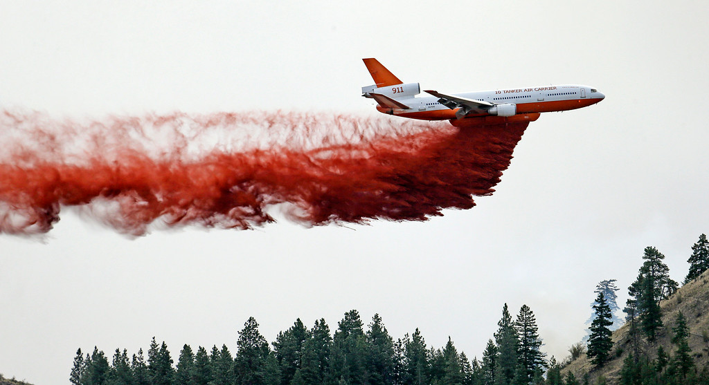 . A DC-10 air tanker drops fire retardant over a wildfire Saturday, July 19, 2014, near Carlton, Wash. A wind-driven, lightning-caused wildfire racing through rural north-central Washington destroyed about 100 homes Thursday and Friday, leaving behind solitary brick chimneys and burned-out automobiles as it blackened hundreds of square miles in the scenic Methow Valley northeast of Seattle. (AP Photo/Elaine Thompson)