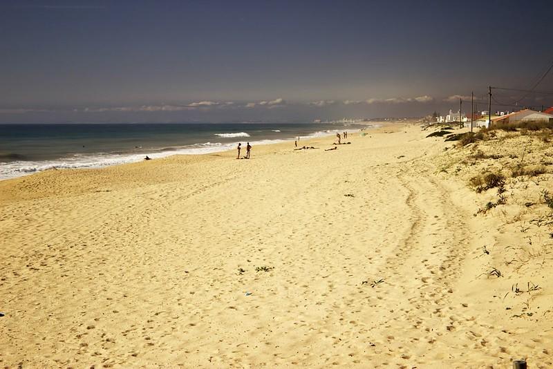 Pohled po pláži na Ilha de Faro směrem na severozápad. Z místa, kde stojíme, se pláž bez přerušení táhne dalších asi patnáct kilometrů, kde je přerušena marínou. Pokud byste tuhle marínu obešli a pokračovali po písečném pobřeží dál, patrně byste se minimálně za odlivu měli celkem reálnou šanci dostat po plážích prakticky suchou nohou až do Albufeiry, vzdálené z místa pořízení fotografie vzdušnou čarou nějakých pětadvacet kilometrů.
