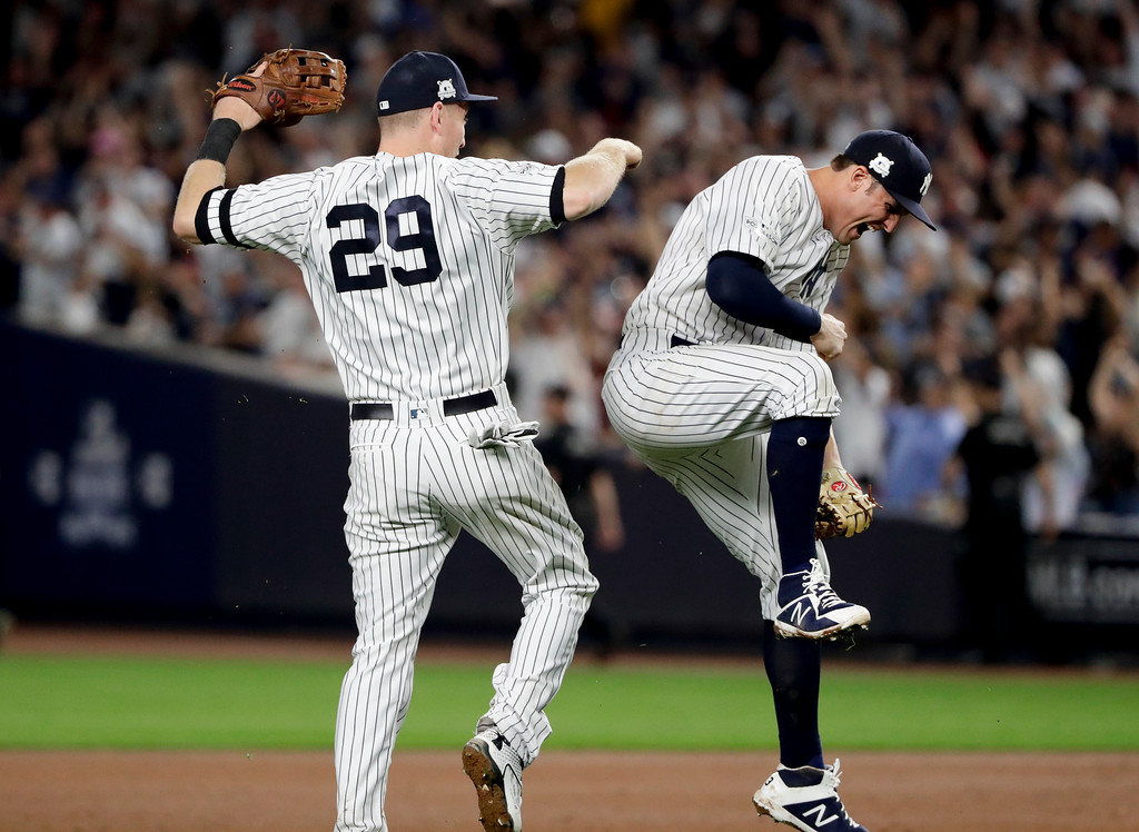 . New York Yankees third baseman Todd Frazier (29) and first baseman Greg Bird (33) celebrate after the Yankees beat the Cleveland Indians 1-0 in Game 3 of baseball\'s American League Division Series, Sunday, Oct. 8, 2017, in New York. (AP Photo/Frank Franklin II)