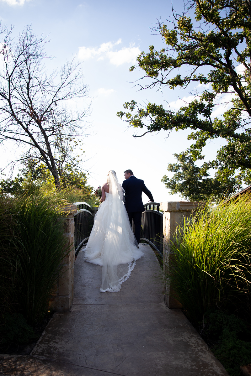a bride being walked down the aisle by her father with the sun shining through trees