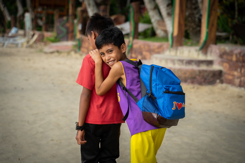 Two children make their commute to school by passing by resorts where tourists lay out in the sand, often blocking areas to walk.