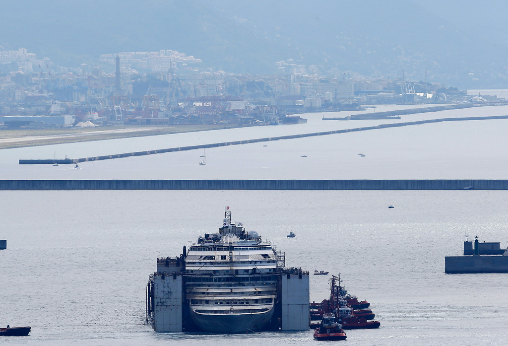 . The wreck of the Costa Concordia cruise ship is towed by tugboats towards Genoa\'s harbor, Italy, Sunday, July 27, 2014. The shipwrecked Costa Concordia cruise liner has completed its final journey. Pulled by tugboats and nudged by brisk winds, the wreck was eased Sunday into Genoa\'s port � where it will be scrapped. The luxury liner struck a reef when its captain sailed too close to Giglio Island off Tuscany\'s coast Jan. 13, 2012, and capsized, killing 32 people. A spectacular operation set the wreck upright in September 2013. On Wednesday, tugboats began the five-day journey to Genoa, headquarters of ship owner Costa Crociere Spa. The wreck will be searched in hopes of finding the remains of an Indian waiter, the only body never found. Ship captain Francesco Schettino is being tried for alleged manslaughter, causing the shipwreck and abandoning the boat with many passengers and crew still aboard.  (AP Photo/Antonio Calanni)