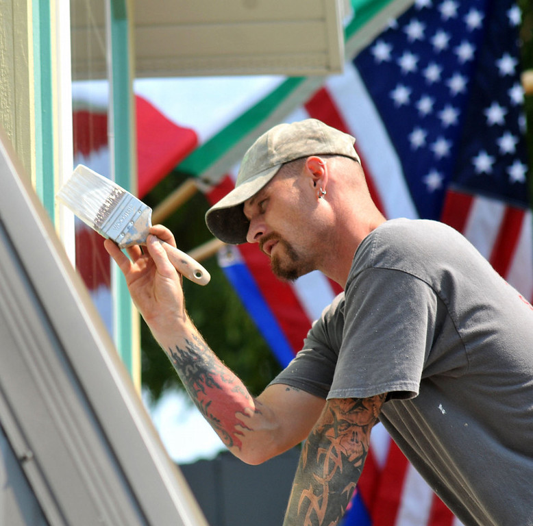 . Travis White from New Richmond, Wis. paints finishing touches on the front facade of the brand new, first time at the Fair, \'Mancinis Al Fresco\' that will feature steak sandwiches, garlic bread, porketta wings, beer on Monday, August 19, 2013.  (Pioneer Press: John Doman)