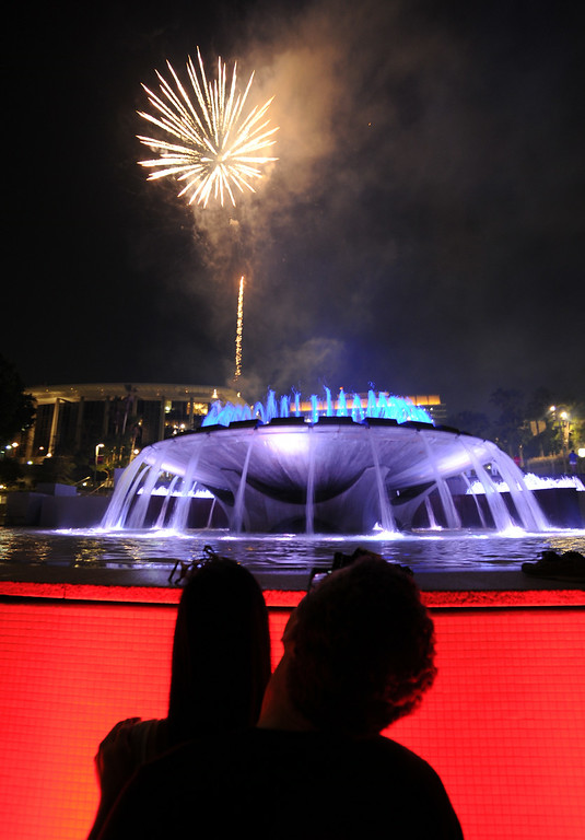 . Fireworks seen over the fountain at Grand Park. Grand Park held its 2nd Annual Fourth of July Block Party featuring music, food and free fireworks. The event was three times larger than the Park\'s first Fourth of July Block Party in 2013. This year, the event covered the entire 12 acres of Grand Park plus adjacent streets, with a footprint extending from Temple Street to 2nd Street and from Grand Avenue to Main Street. The event was designed to accommodate 25,000 people. Fireworks were shot off from the roof of the Dorothy Chandler Pavilion at The Music Center. Los Angeles, CA. 7/4/2014(Photo by John McCoy Daily News)