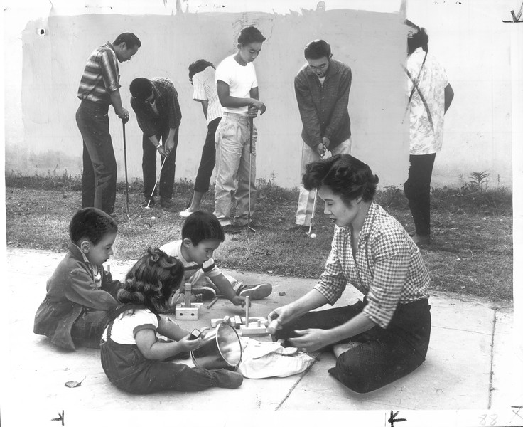 """""""Help Here -- some of the flock of young people who regularly gather at her Long Beach home-recreational center practice golf swings behind Mrs. Sue Joe.  She plays with David Ater and her Rand, 3, Lisa, 1.""""--caption on photograph"""