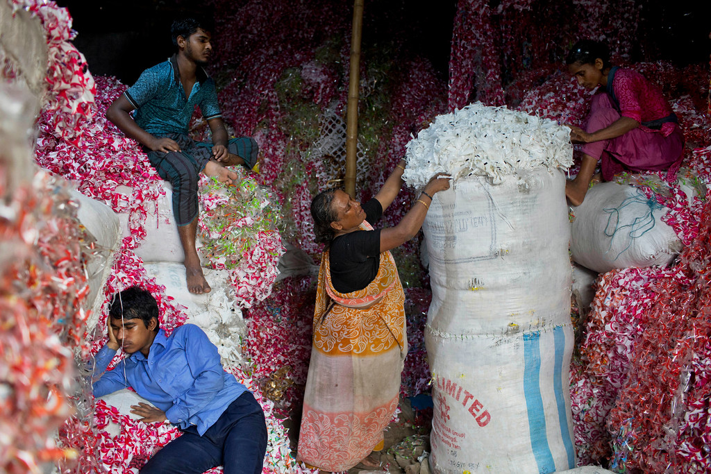 ". Bangladeshis work at a plastic strips storehouse in Dhaka, Bangladesh, Monday, June 4, 2018. The theme for this year\'s World Environment Day, marked on June 5, is ""Beat Plastic Pollution.\"" (AP Photo/A.M. Ahad)"
