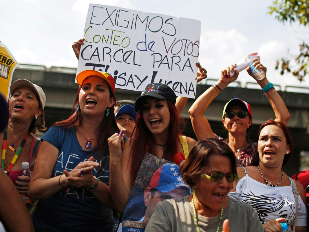 ". Supporters of opposition leader Henrique Capriles demonstrate in front of his campaign headquarters with a sign that reads, ""We demand a vote recount,\"" in Caracas, April 15, 2013. Capriles on Monday called on Venezuelans to take to the streets and peacefully demand a vote recount if election authorities formally proclaim Hugo Chavez\'s chosen successor, Nicolas Maduro, as the next president.  REUTERS/Tomas Bravo"