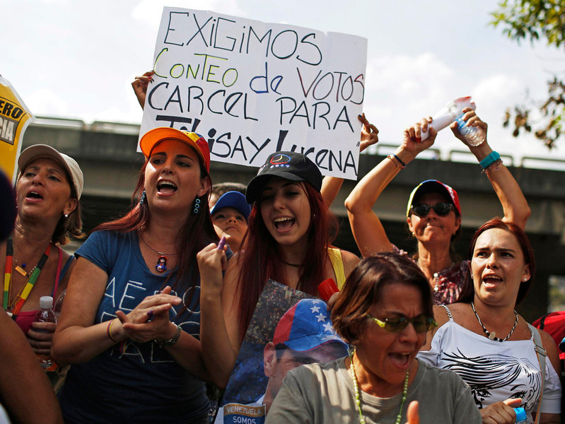 """. Supporters of opposition leader Henrique Capriles demonstrate in front of his campaign headquarters with a sign that reads, \""""We demand a vote recount,\"""" in Caracas, April 15, 2013. Capriles on Monday called on Venezuelans to take to the streets and peacefully demand a vote recount if election authorities formally proclaim Hugo Chavez\'s chosen successor, Nicolas Maduro, as the next president.  REUTERS/Tomas Bravo"""