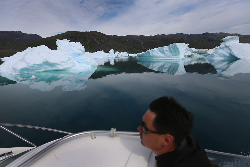 . Kunuk Nielsen navigates his boat among calved icebergs from the nearby Twin Glaciers on July 31, 2013 in Qaqortoq, Greenland.  (Photo by Joe Raedle/Getty Images)