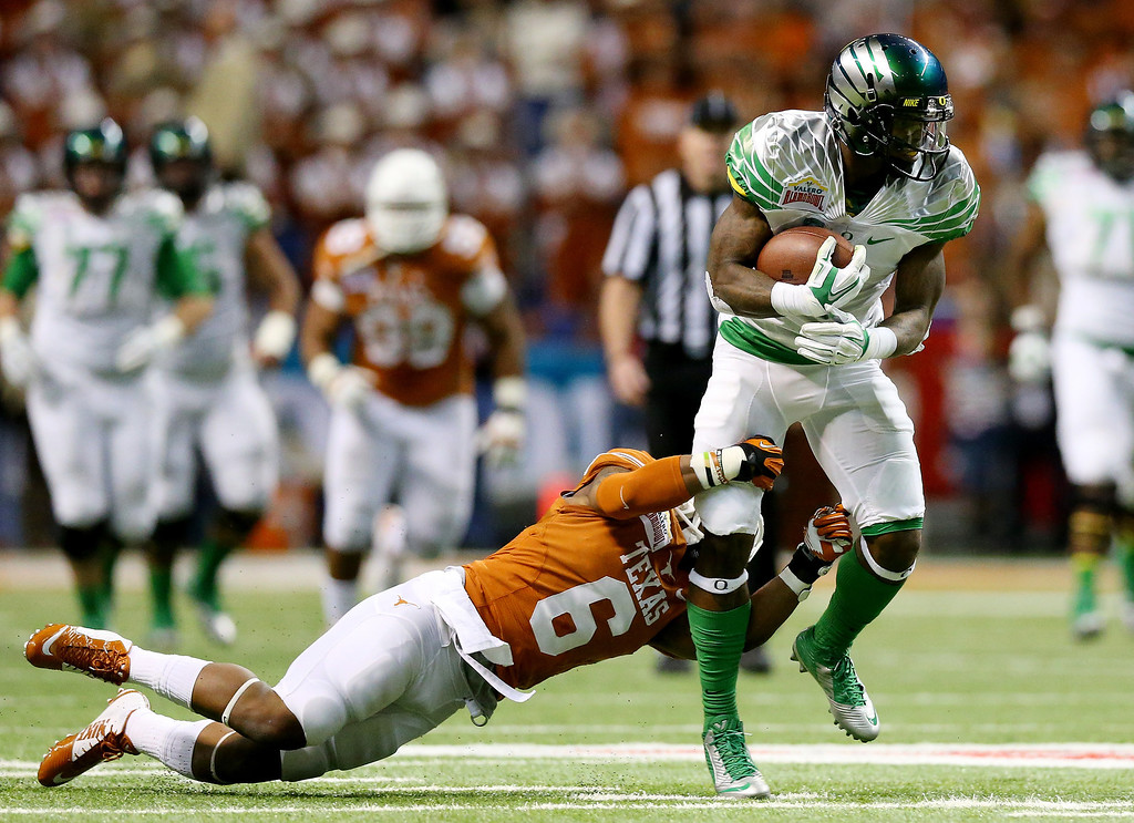 . Wide receiver Josh Huff #1 of the Oregon Ducks is tackled by cornerback Quandre Diggs #6 of the Texas Longhorns during the Valero Alamo Bowl at the Alamodome on December 30, 2013 in San Antonio, Texas.  (Photo by Ronald Martinez/Getty Images)