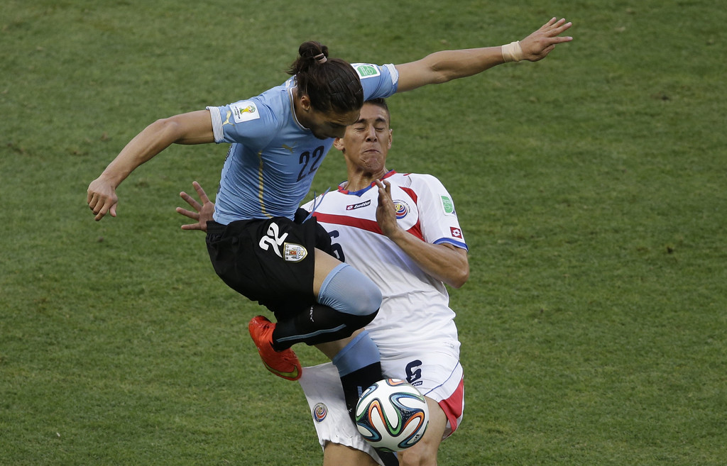 . Uruguay\'s Martin Caceres, left, and Costa Rica\'s Oscar Duarte, right, challenge for the ball during the group D World Cup soccer match between Uruguay and Costa Rica at the Arena Castelao in Fortaleza, Brazil, Saturday, June 14, 2014.  (AP Photo/Sergei Grits)